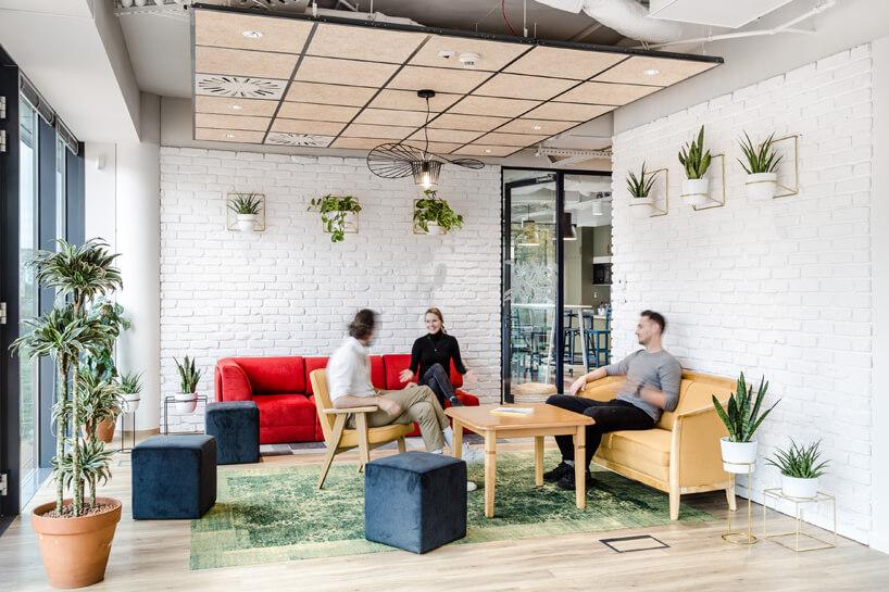 ekologiczne biuro od workplace solutions przestrzeń do relaksu zbiałą cegiełką na ścianach zroślinami wpomieszczeniu