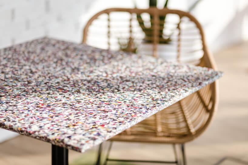 ekologiczne biuro od workplace solutions mały stolik zblatem zsurowców na tle wiklinowego krzesła