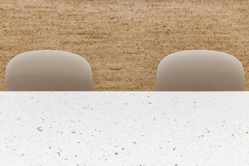 ekologiczne biuro od workplace solutions jasny blat zsurowców zdwoma krzesłami na tle korkowej ściany