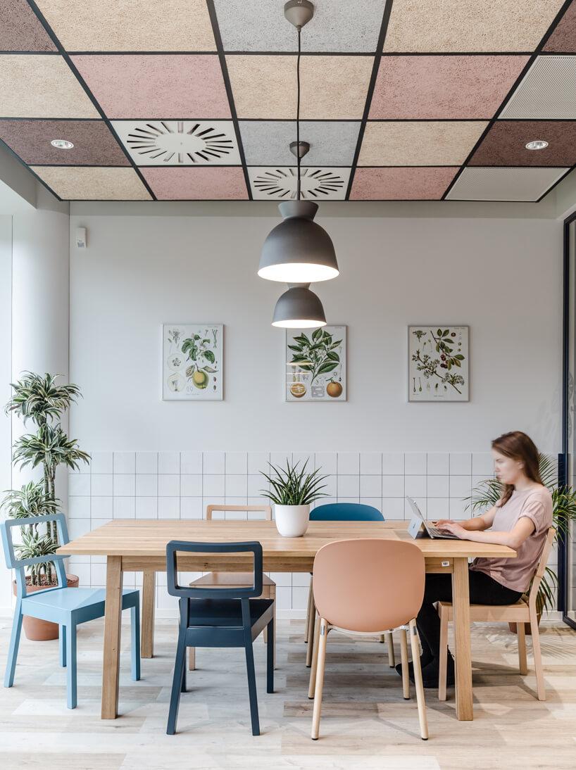 ekologiczne biuro od workplace solutions biała przestrzeń zdużym drewnianym stole zkolorowymi krzesłami na tle białej ściany zplakatami owoców
