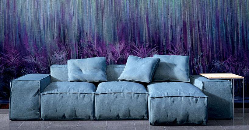niebieska sofa na tle tapety zmotywem fioletowych traw