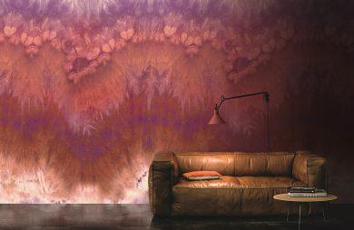 brązowa skórzana kanapa na tle wyjątkowej tapety fioletowo-czerwono-białej