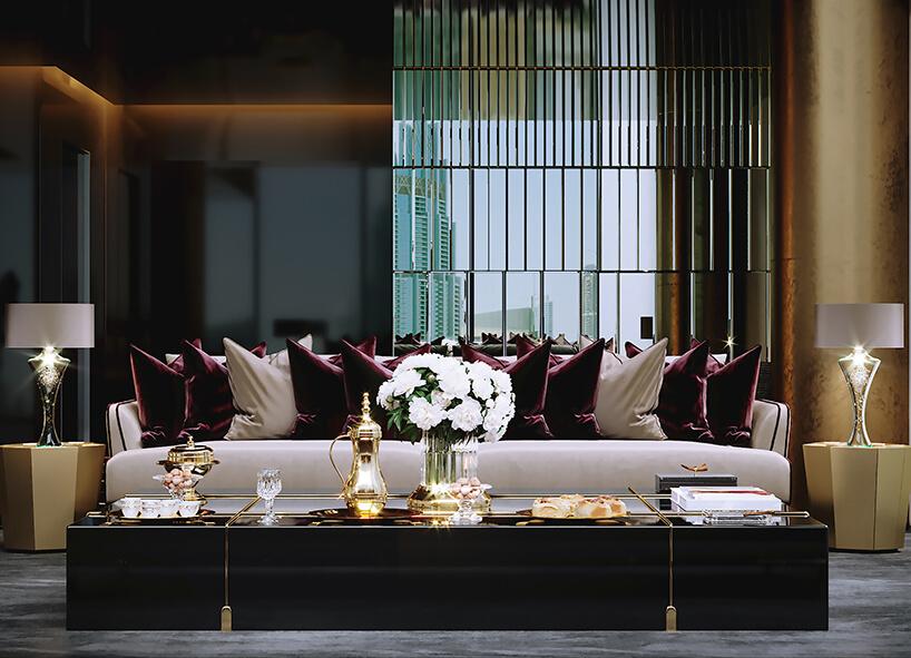 luksusowe wnętrze apartamentu wDubaju od Covet House niski czarny stół ze złotymi wykończeniami wciemnym salonie