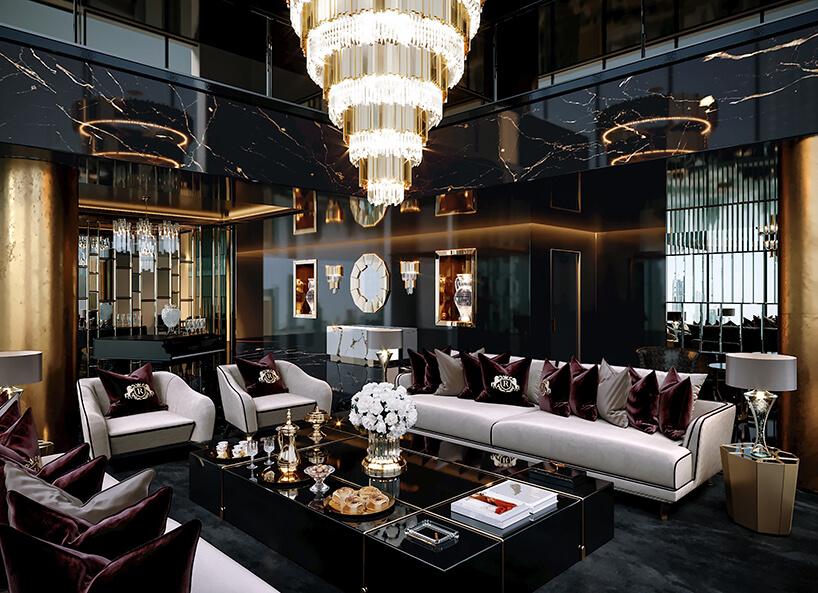 luksusowe wnętrze apartamentu wDubaju od Covet House czarno-złoty salon zbiałą dużą sofą idużym złotym żyrandolem