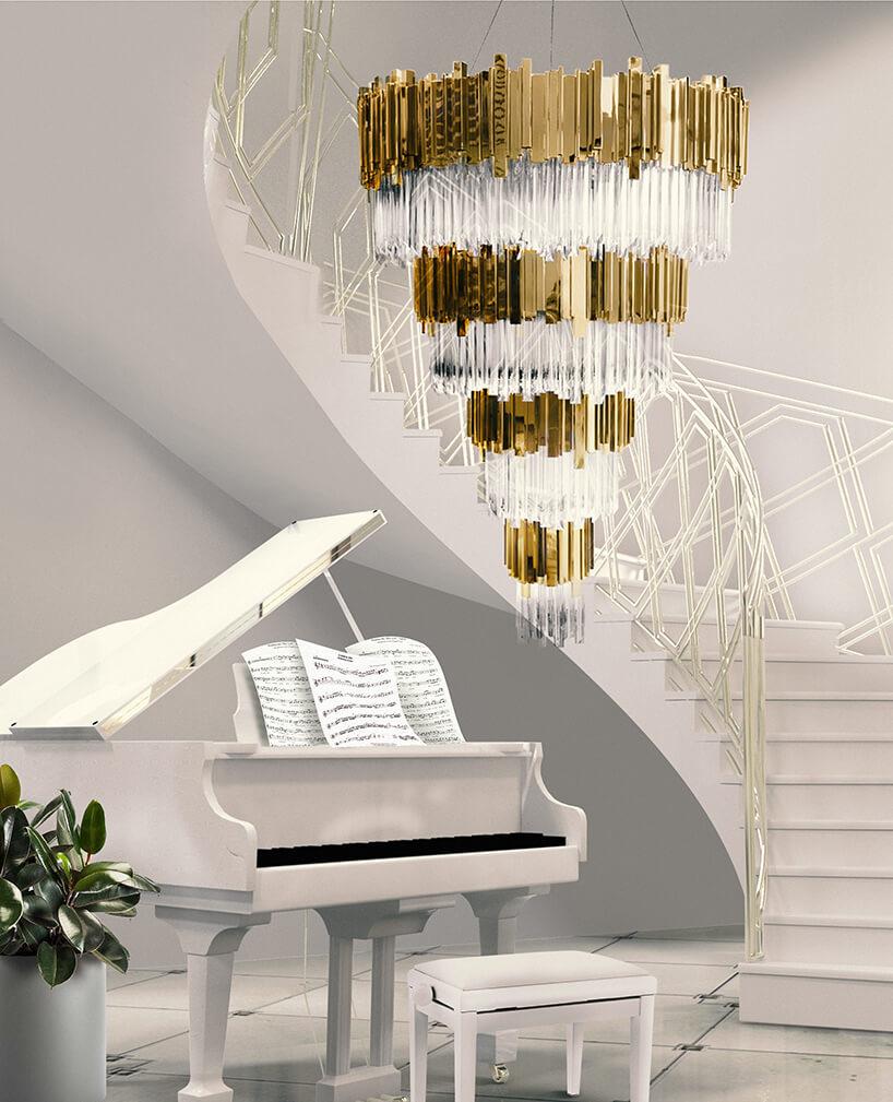 luksusowe wnętrze apartamentu wDubaju od Covet House białe kręcone schody jako tło dla złotego żyrandolu ibiałego fortepianu