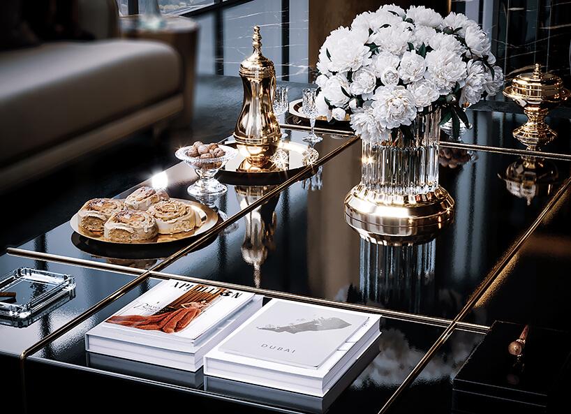 luksusowe wnętrze apartamentu wDubaju od Covet House czarny stół ze złotymi akcentami ze złotymi naczyniami