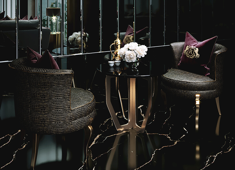 luksusowe wnętrze apartamentu wDubaju od Covet House zielone fotele ze złotym wykończeniem inogami przy czarnym małym stoliku ze złota podstawą na tle ciemnego pomieszczenia