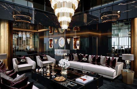 luksusowe wnętrze apartamentu w Dubaju od Covet House czarno-złoty salon z białą dużą sofą i dużym złotym żyrandolem