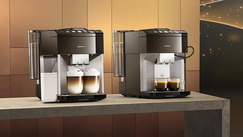 dwa ekspresy ciśnieniowe do kawy Siemens zserii EQ.500 na szarym blacie na tle matowej złotej ściany