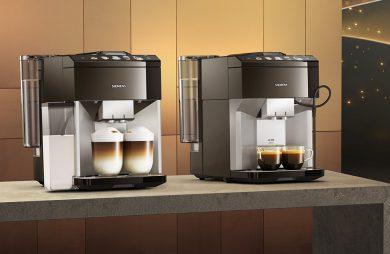 dwa ekspresy ciśnieniowe do kawy Siemens z serii EQ.500 na szarym blacie na tle matowej złotej ściany