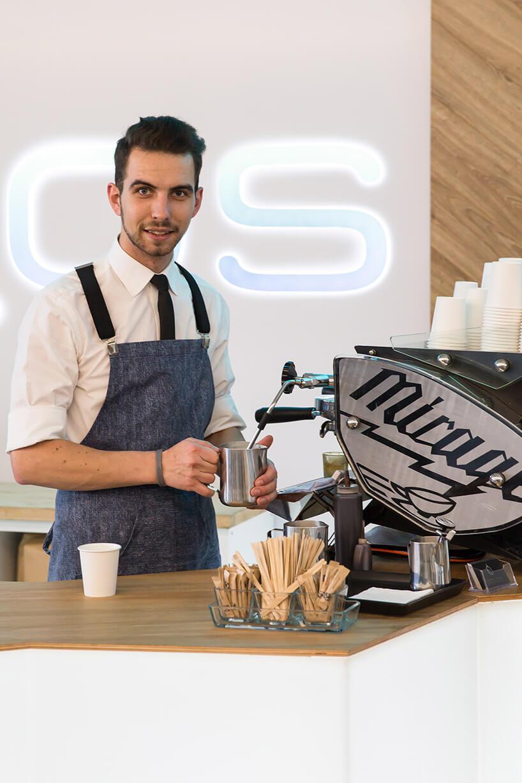 mężczyzna wniebieskim fartuchu przy ekspresie do kawy