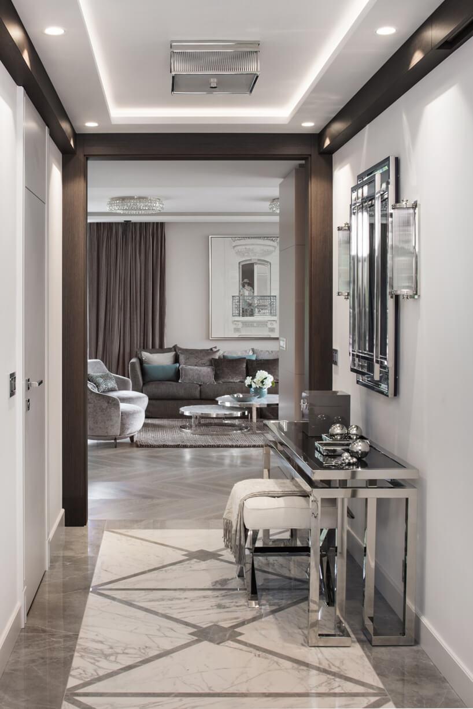 eleganckie wnętrze apartamentu projektu Rolanda Stańczyka biały przedpokój zbrązowymi elementami imały chromowany stolik pod lustrem