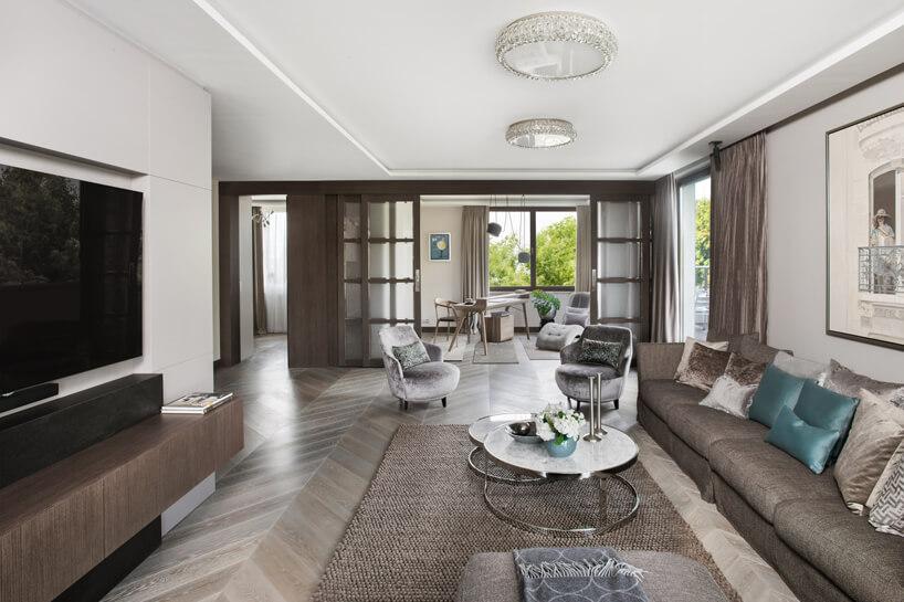 eleganckie wnętrze apartamentu projektu Rolanda Stańczyka przestronny biały salon zdługą brązowo sofą przy niskim stoliku zbiałym okrągłym blatem