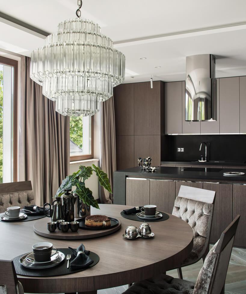 eleganckie wnętrze apartamentu projektu Rolanda Stańczyka elegancki duży ciemny stół zkrzesłami pod dużym żyrandolem na tle ciemno brązowej kuchni
