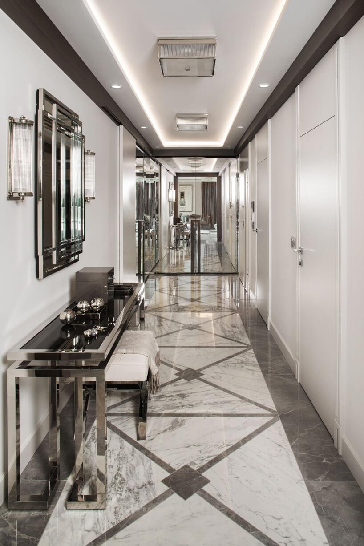 eleganckie wnętrze apartamentu projektu Rolanda Stańczyka biały hol zkamienną podłogą ilustrzanymi drzwiami na końcu