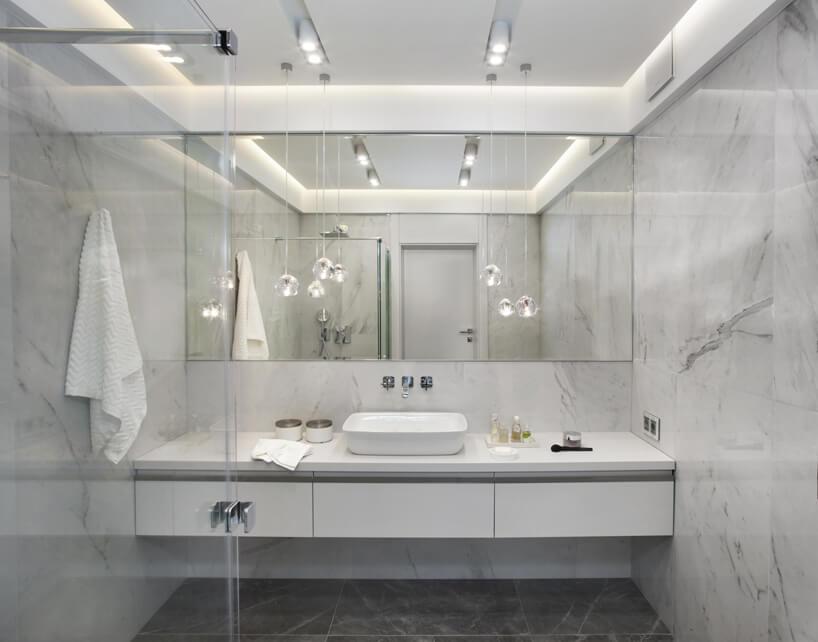 eleganckie wnętrze apartamentu projektu Rolanda Stańczyka biała łazienka zlustrem na całą ścianę za umywalką