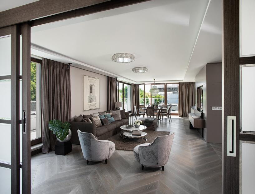 eleganckie wnętrze apartamentu projektu Rolanda Stańczyka jasny salon zbrązowymi zasłonami dużą sofą idwoma biało szarymi fotelami
