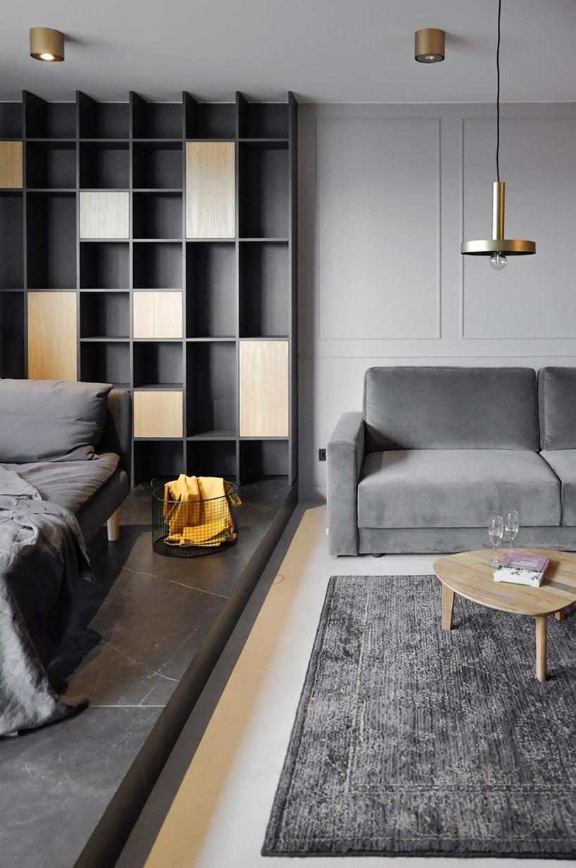 nowoczesny apartament od mauve zszarą sofą iniskim drewnianym stolikiem