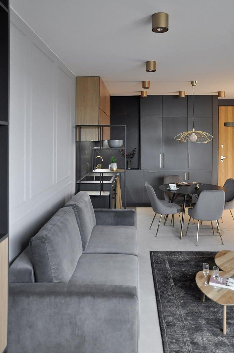 nowoczesny apartament od mauve salon obok aneksu kuchennego zciemnym okrągłym stolikiem