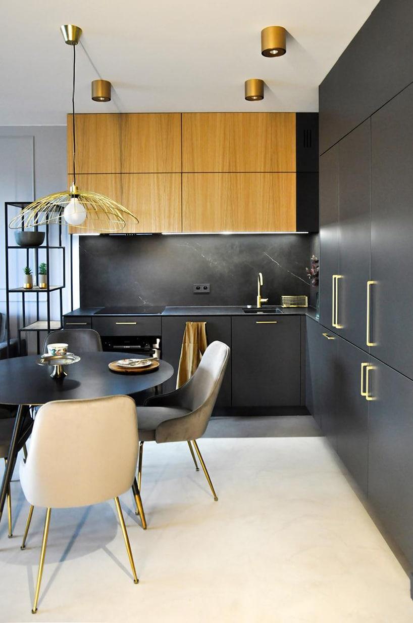 nowoczesny apartament od mauve czarny aneks kuchenny zdrewnianym akcentami izłotymi uchwytami