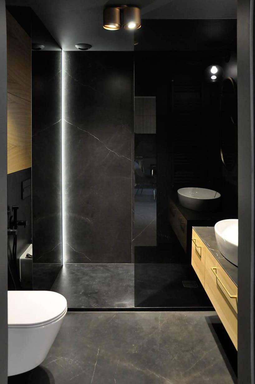 nowoczesny apartament od mauve elegancka czarna kamienna łazienka zprysznicem