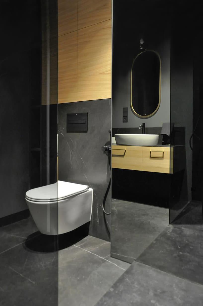 nowoczesny apartament od mauve elegancka ciemna kamienna łazienka zdrewnianymi akcentami