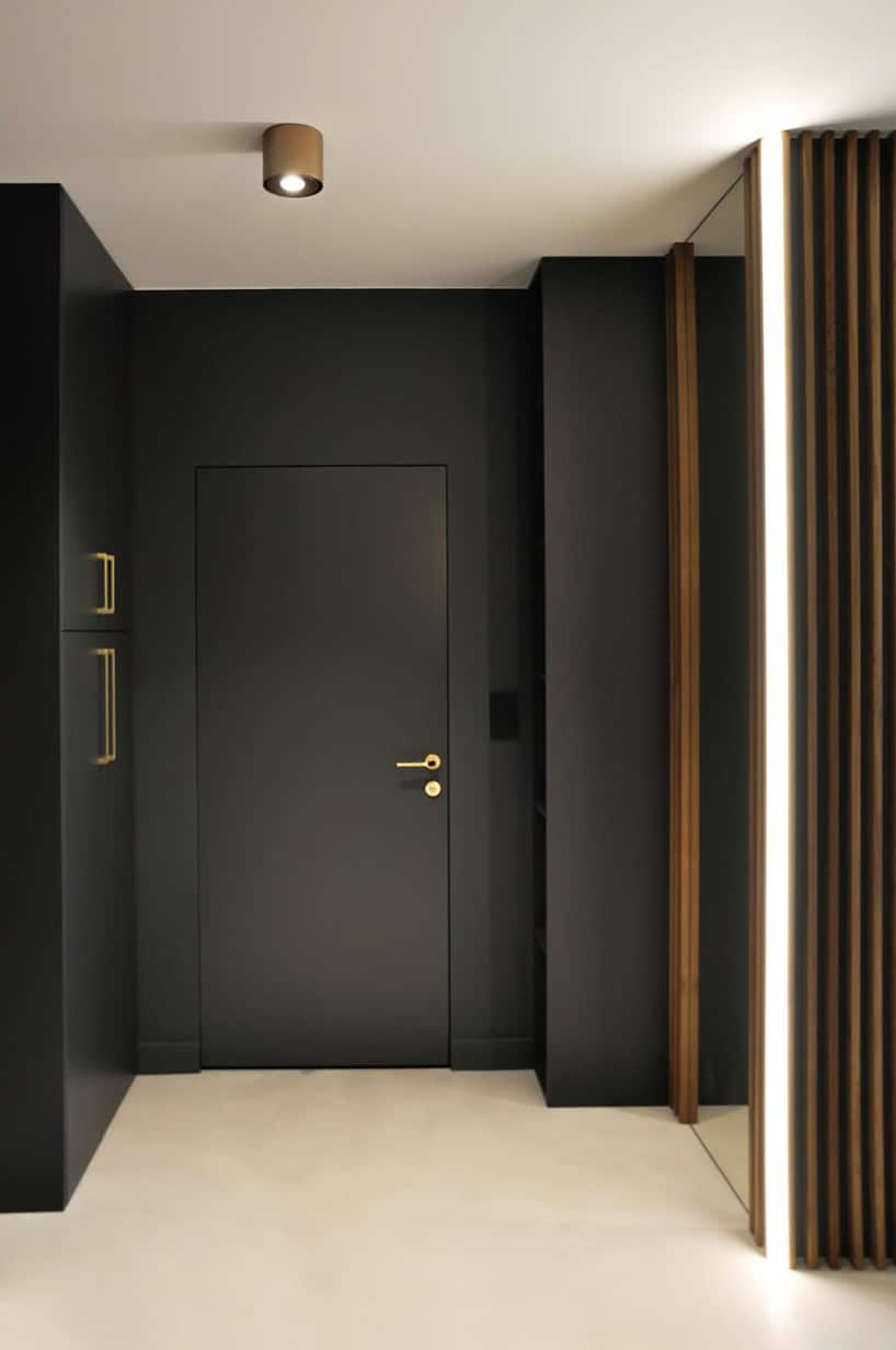 nowoczesny apartament od mauve czarny przedpokój zdużym lustrem izłotymi klamkami iuchwytami