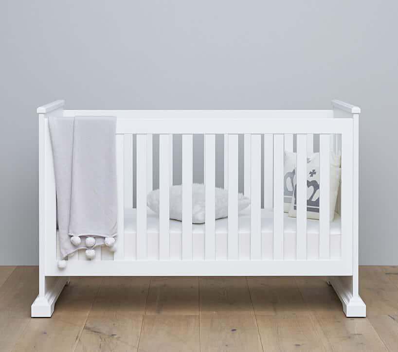 eleganckie białe łóżeczko dla dziecka od Nizio Home na drewnianej podłodze na tle szarej ściany