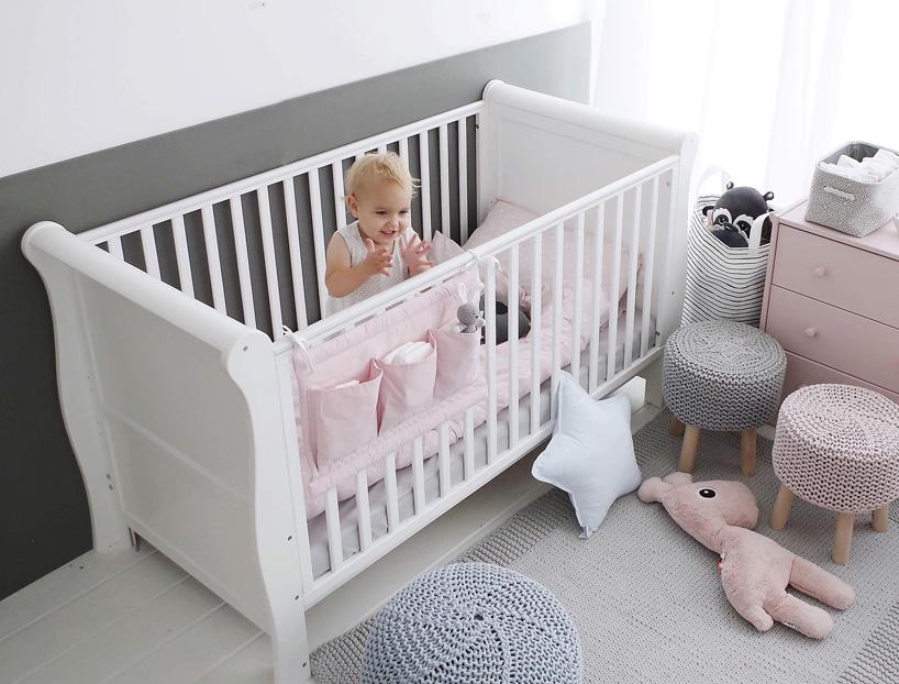 białe ładne drewniane wysokie łóżeczko od Woodies Safe Dreams dla dziecka zróżową pościelą imałą dziewczynką wśrodku