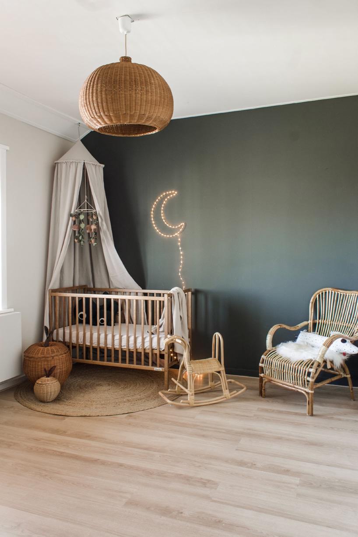 drewniane eleganckie łóżeczko od Woodies Safe Dreams wdużym pokoju zciemnozieloną ścianą iświecącym księżycem