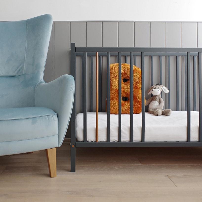 eleganckie szare łóżeczko od Woodies Safe Dreams zwyjętymi szczebelkami obok niebieskiego fotela
