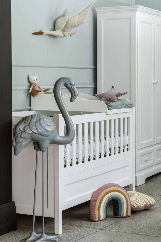 biały zestaw mebli dziecięcych od NIZIO HOME łóżeczko zprzewijakiem na tle szafy
