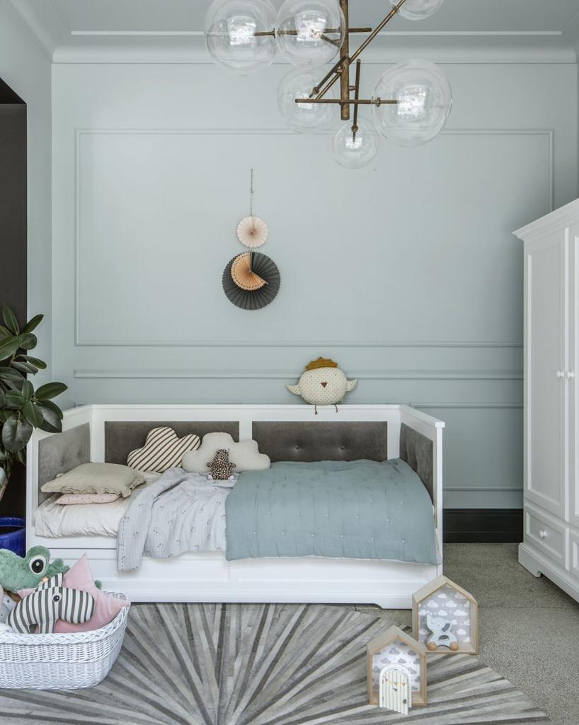 elegancki biały zestaw mebli dziecięcych od NIZIO HOME wpokoju zjasno zielonymi ścianami