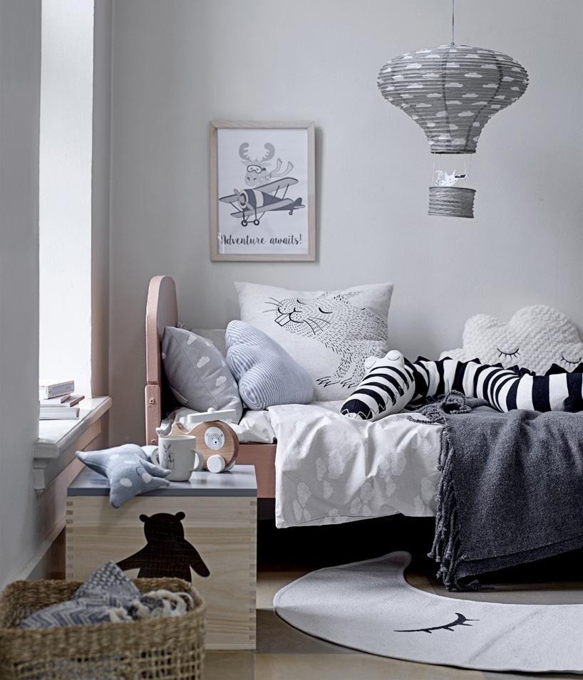 drewniane łóżko dziecięce obok drewnianej szafki pod lampą zżyrandolem wkształcie balonu