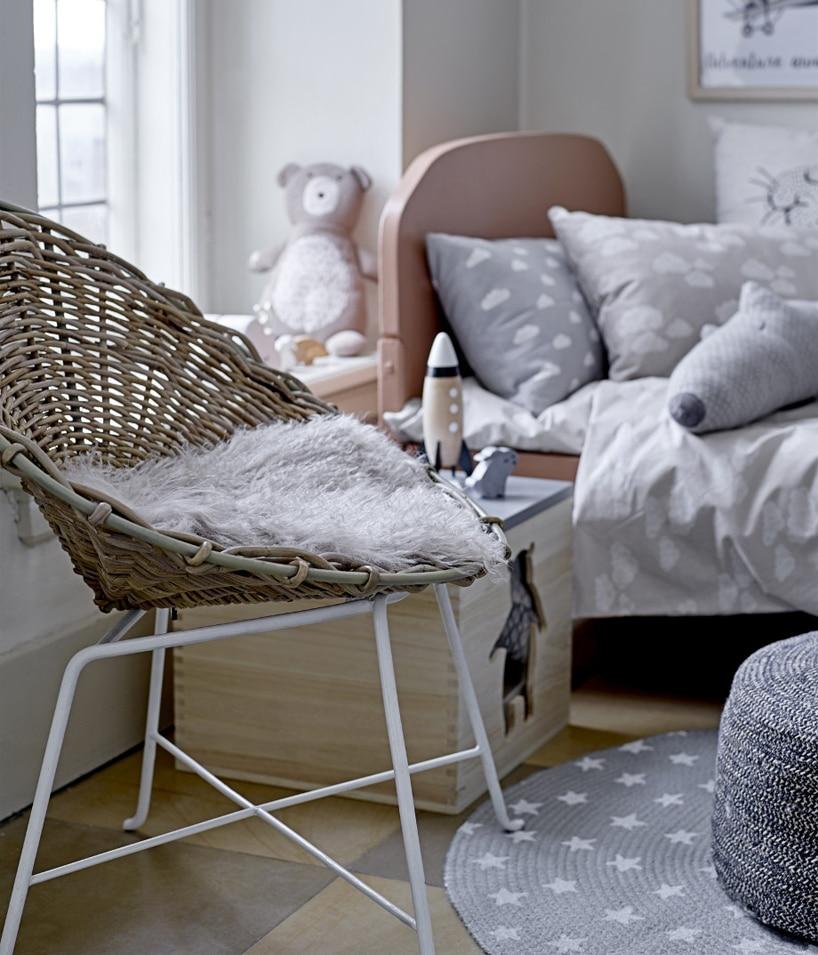 plecione krzesło na tle drewnianej szafki iłóżka dla dzieci