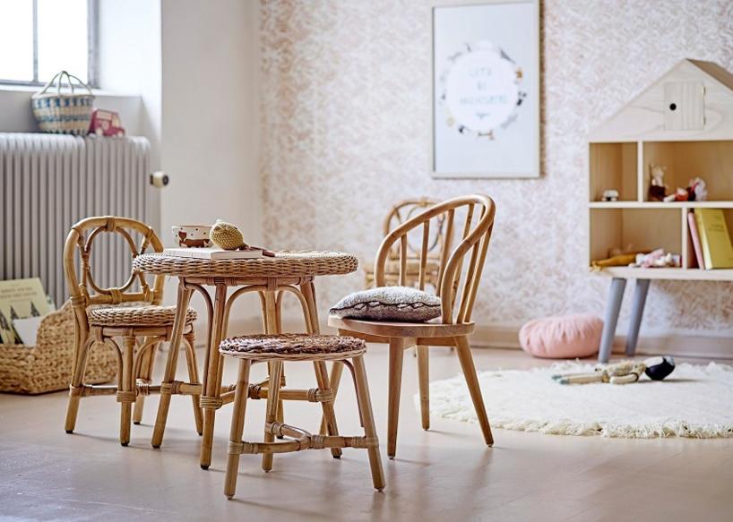 zestaw małych drewnianych mebli dla dziecka krzesła zoparciem ze stołkiem na tle wytapetowanej ściany