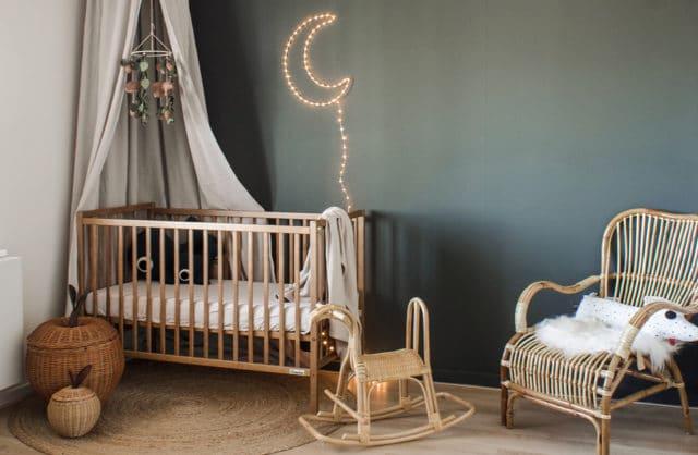 drewniane eleganckie łóżeczko od Woodies Safe Dreams w dużym pokoju z ciemnozieloną ścianą i świecącym księżycem