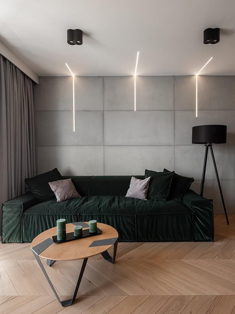 zielony narożnik Cushions od Rosanero waranżacji salonu zdrewnianą podłogą przy drewniano metalowym małym stoliku