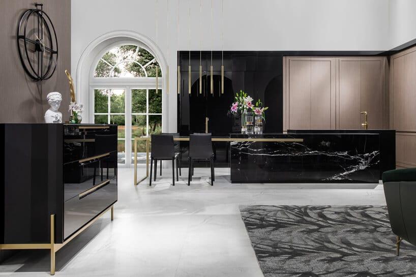 luksusowa kuchnia od ernestrust biała zczarnymi meblami dużą czarną wyspą kuchenną ze złotymi akcentami