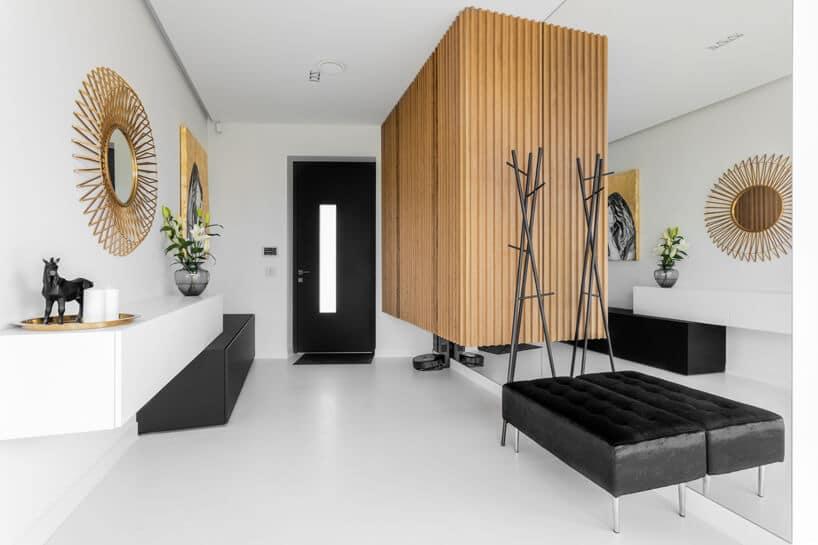 elegancka biała garderobą zdrewnianą zabudową iczarnym siedziskiem na tle lustra na całej ścianie