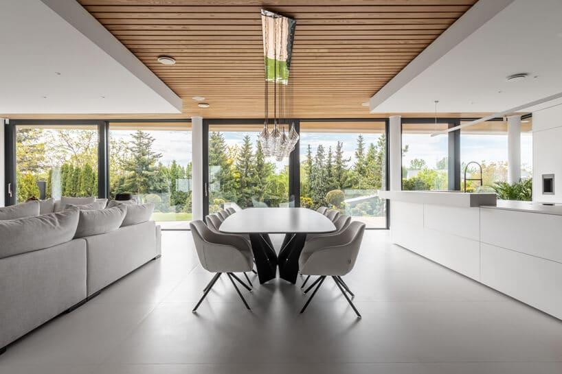 elegancki biały biało czarny stół zkrzesłami pomiędzy jasną sofą wsalonie abiałą kuchnią