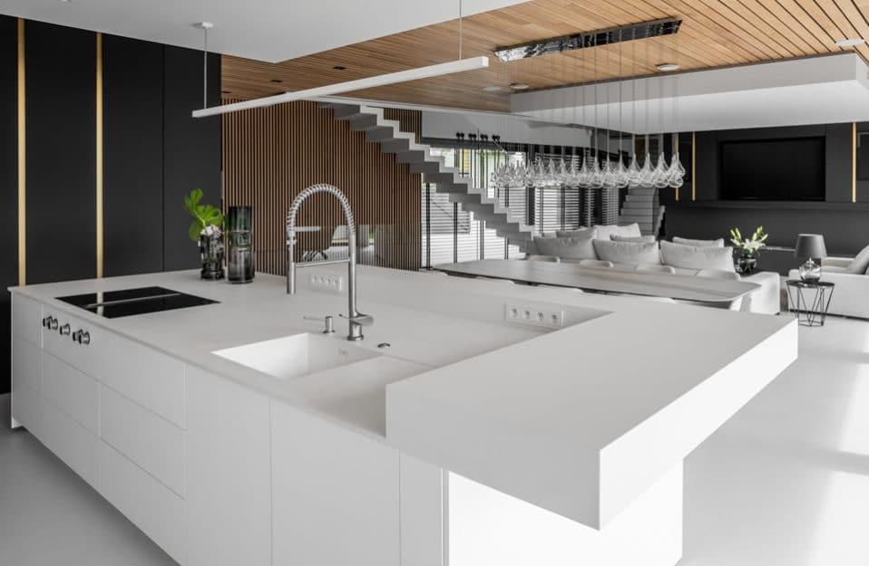 biała duża wyspa kuchenna na tle stołu jadalnego i salonu