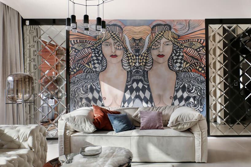 elegancka jasna sofa na tle dużego obrazu zdwoma kobietami
