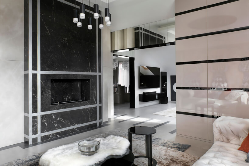 nowoczesne wnętrze salonu kominkiem obudowanym szarym kamieniem
