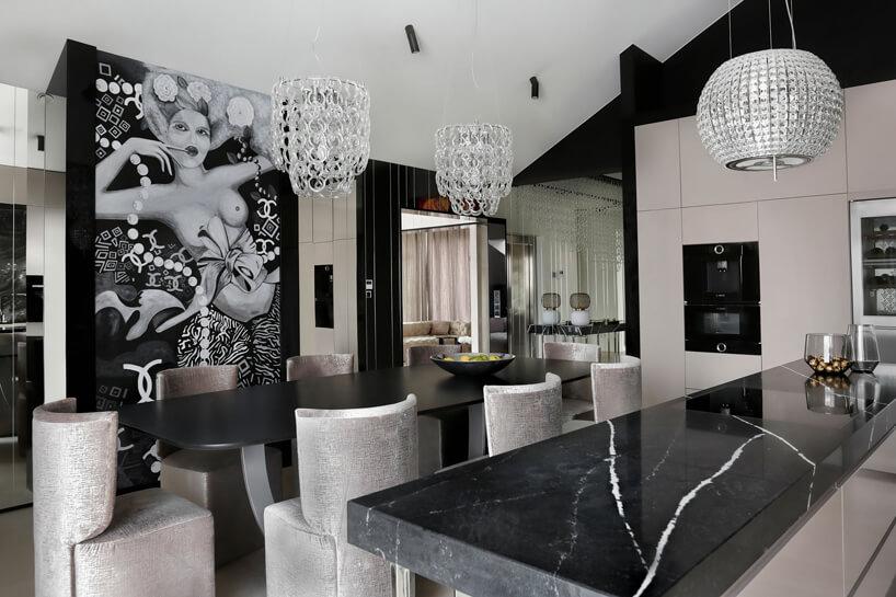 elegancka jadalnia cz czarnym stołem isrebrnymi krzesłami na tle czarno białego obrazu kobiety na ścianie