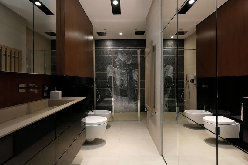 elegancka łazienka zjasną podłogą zczarną ibrązową ścianą na tle mozaik pod prysznicem zmotywem kobiety