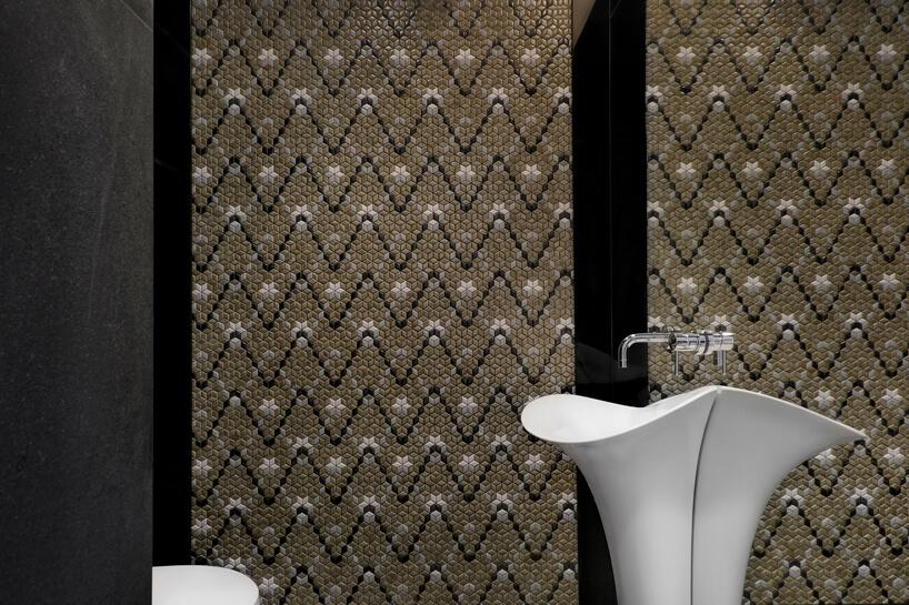 elegancka umywalka na ścianie wykończonej lustrem na tle brązowej szarej iczarnej mozaiki