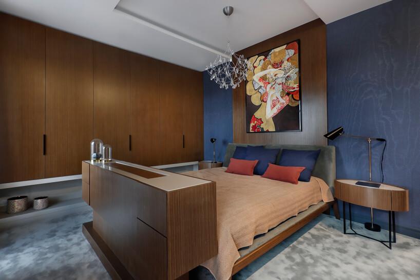 nowoczesna elegancka sypialnia zniebieskimi ścianami duzym łóżkiem zdrewnianą zabudową