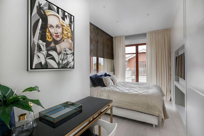 jasna sypialnia zdużym obrazem kobiety nad czarno złotym stolikiem