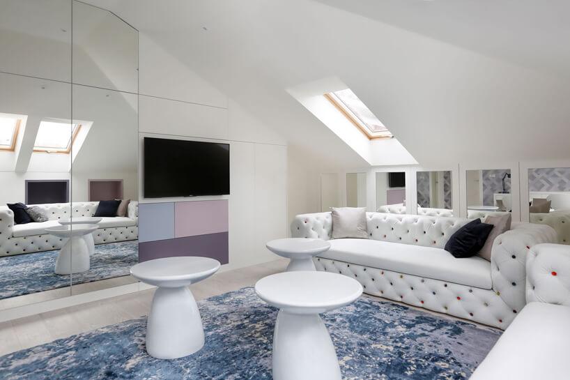 nowoczesny pokój dla dzieci na poddaszu zbiałymi błyszczącymi stolikami idwoma białymi sofami zkolorowymi guzikami